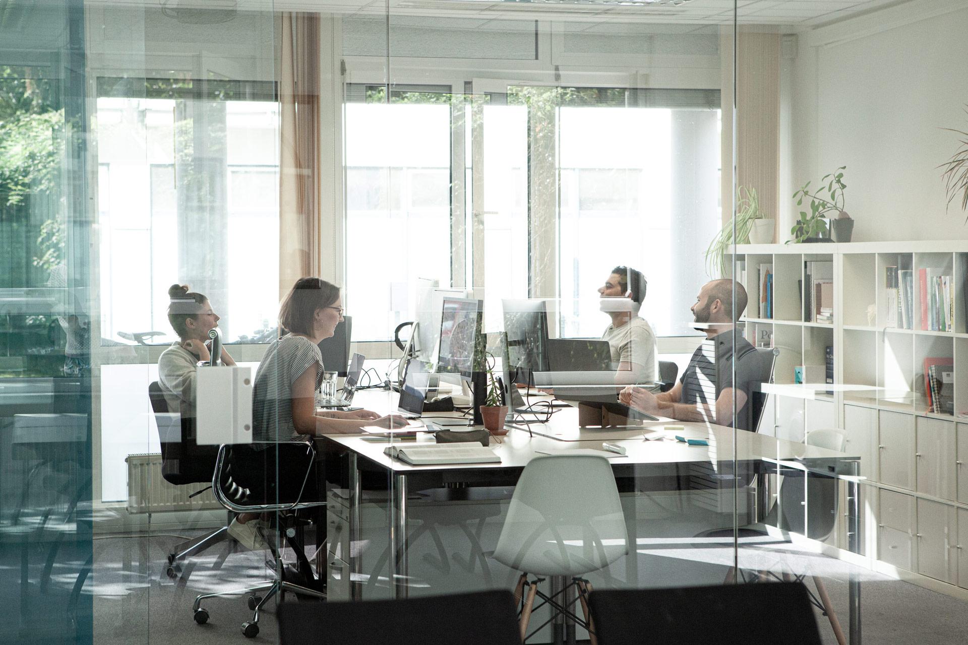 Foto von Steffen Gorski, Lea Wigger und Kolleginnen, die gemeinsam am Schreibtisch arbeiten